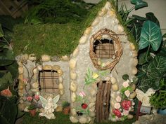 I started with pieces of cardboard and constructed the shape of a house.  Then quite a few layers of concrete.  Added some small stones, and a stick door, a few flowers, butterflies, and a moss roof.