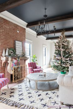 A gorgeous living room restoration reveal... Black ceilings, dark wood beams, shag rug, tufted sofa and Christmas decor create a stunning vintage space.