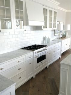 I want this kitchen..... white subway tile + glass-front cabinets + wood flooring + marble counter