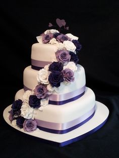 3 tier heart shaped wedding cake. roses cascading down with a purple theme.