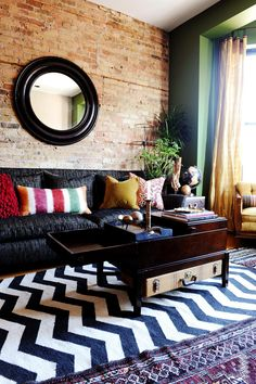 Eclectic Living Room With Green Accent Wall Several patterns and a rich color scheme were the focus of designer SuzAnn Kletzien's plan for this eclectic living room. A vibrant green accent wall frames the bay window area, while a brick wall provides a rustic edge behind a soft black chenille sofa. Kletzien paired together a black vintage Persian rug with two other rugs, including one with a modern blue-and-white chevron design, to create a layered look.