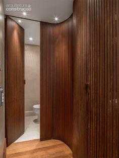 CURVA DE AÇO. O elemento-surpresa é esta sinuosa divisória de aço corten. Fixada em trilhos soldados ao piso e ao teto, a estrutura de 3,40 m de comprimento abriga, de um lado, boiler, louceiro e nichos para os eletrodomésticos. Do outro, dá acesso ao lavabo e à área de serviço. Projeto de Atria Arquitetos.