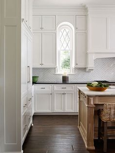 Beautiful kitchen features a stained island topped with calcutta marble lined with wicker counter stools.