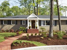 """""""When I pull into the driveway, I finally think, Wow, that's a nice house,"""" says Nick. He and Catherine painted the exterior stone gray and adding a gabled portico over the existing stoop. They installed custom shutters, a new shingle roof, and a brick walkway. The tidy front yard is fully landscaped with boxwoods, Ruby Chinese fringe flower, windmill palms, and mature pine trees. The custom mahogany front door has six windows to let in light."""