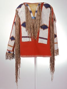 Ute shirt ca. 1870-1880. One of the first horse cultures of the West, the Ute people traded horses from the Southwest to the central Plains and Plateau. They freely adopted from the tribes they encountered, as seen in this man's red wool trade-cloth shirt, ornamented with buckskin fringe and wide bands of lazy-stitch beadwork. The wide, beaded strips resemble Plains styles of beadwork while the geometric patterning within and around the neckpiece uses colors used by tribes west of the…