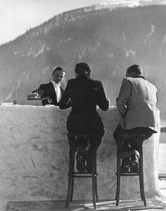 A British couple sitting on high stools at the ice bar of the Grand Hotel in St Moritz, Switzerland 1932