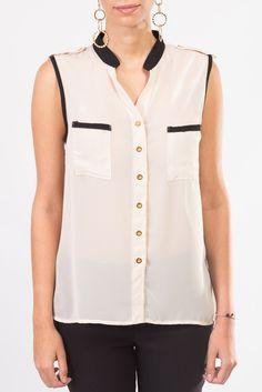 Esta blusa crema con detalles en negro y botones dorados sin mangas es perfecta para lucir fabulosa en la oficina.