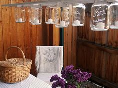 Hang 8 mason jars from a wooden plank for a rustic outdoor chandelier #masonjars