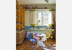 Ao lado da TV, no family room, os livros ficam sobre a mesa Saarinen preta. As cadeiras em um tom forte de amarelo, escolhidas pela proprietária e arquiteta Valéria Blay, destacam-se no ambiente, ao lado do cadeirão gigante