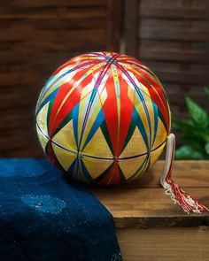 """Temari (手まり) were originally introduced in Japan in the 7th century. The balls are meticulously handmadewith tightly wrapped fabric and thread, displaying brilliant colors and patterns. Some are wrapped so tightly that they are able to bounce. They were traditionally given to children by their mothersas a New Years' gift, and represent deep love, friendship, and loyalty.  Origin: Japan Diameter: 9"""" Product #:TM01 Code: WP25"""