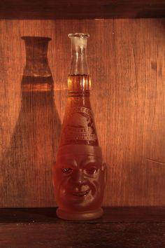 Kentucky Coon – Raríssima garrafa figurativa duas faces de vidro um lado está sorrindo e o outro chorando
