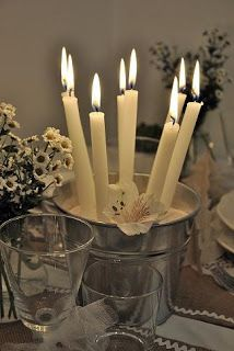 Taper candles in sand & bucket.