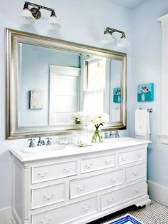 elegant bath combines pale blue walls with an oversize silver-framed mirror and silvertone fixtures to create a look of luxury. A large white-painted vintage dresser was repurposed as a vanity by adding a white slab countertop, twin oval sinks, and vintage-look faucets with cross handles. original hexagonal tile . Clear glass vases and jars add a bit of sparkle