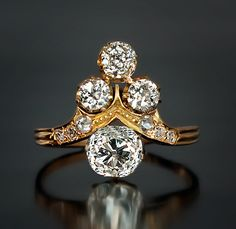 A Belle Époque Ladies Diamond Ring, circa 1890. An 18K yellow gold tiara shaped ring is prong set with two antique cushion cut and two old European cut diamonds. The largest stone is a bright white 1.35 ct cushion cut diamond, G color, VS2 clarity. The shoulders of the ring are embellished with six rose cut diamonds. Estimated total diamond weight 2.20 ct.
