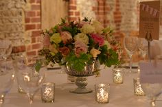 Upwaltham Barn, round tables decorated with low mercuried glass dishes filled with a mound of roses, seasonal flowers and foliages, add to the sparkle with candles in matching votives