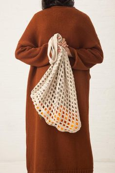 """Open knit crochet net bag. Oversized. Made by hand in Peru. 60% cotton, 40% linen. 15"""" W x 16"""" H x 3.5"""" D; 10"""" strap drop. A quiet and consummate creator of bea"""