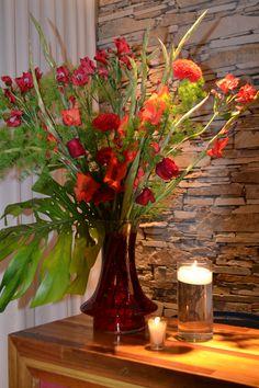 Jarron en altura con flores rojas acompañado por tubines con velas