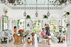 Decorator Celerie Kemble, financier Boykin Curry, and their children (from left, Rascal, Wick, and Zinnia) gather in the clubhouse of Playa Grande Beach Club, a compound she created in the Dominican Republic. The chandeliers were custom made locally, and the wicker armchairs are vintage.