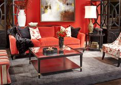 Red sofa by Burton James compliments the grey steel and glass coffee table.