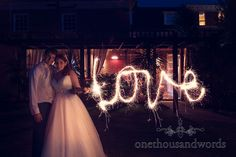 Wedding couple write love with sparkler at Bournemouth Hotel Wedding. Photography by one thousand words wedding photographers