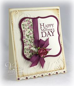 By Julee Tilman. Glued designer paper onto cardstock, then cut with die. Added ribbon, bow, embellishments. Die-cut mat. Dry embossed layer with distressed, inked edges. Card base punched at bottom, edges inked. Rhinestones added to punched area. Very pretty!