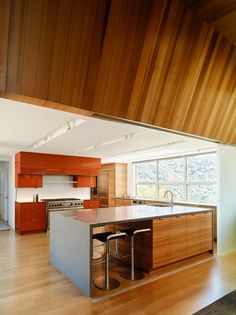 In this modern kitchen, a large island with seating provides plenty of counterspace, while wood cabinets compliment the wood ceiling in the dining room. #ModernKitchen #WoodCeiling #LargeKitchenIsland #KitchenDesign