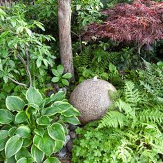 A granite sphere fountain, tucked between ferns and hostas, brings the subtlest murmur of water to this side garden. | Photo: Mark Lohman | thisoldhouse.com