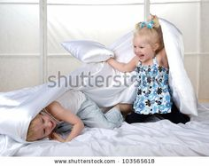 Happy  kids  having fun with pillows on bed - stock photo