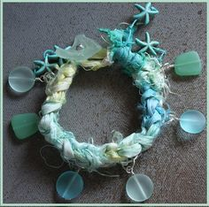 Crochet Sari Silk Ribbon onto a silver plated chain. Resin Sea Glass beads Dangle from the chain with Howlite Starfish accents. Closure is a soft green sea glass button.