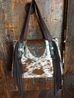 A Bonnie Bag with a turquoise suede steer on the flap, straps with side fringe,turquoise leather lace stitching, and conchos. Custom purses and totes from gowestdesigns.us