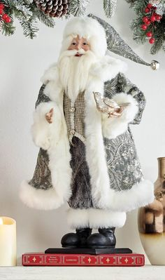 Sure to make your holiday entertaining space all the merrier, this festive Santa is resplendent in a fur-lined royal pewter jacket and hat and holds a glittering bird in his hand. Hand-sculpted by highly skilled artisans.
