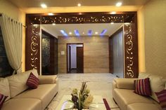 Wooden panelling arund the opening and marble cladded wall on the other side with concealed lights on the false ceiling makes this entrance bright and inviting. Ceiling Design Living Room, Living Room Partition Design, Room Partition Designs, Room Door Design, False Ceiling Design, Living Room Designs, Living Room Decor, Wooden Partition Design, Home Design