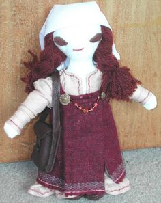 INGMAR is the first of the costume dolls. Ingmar is an 8th century Viking lady wearing an embroidered linen kyrtle, a woollen hangerok with bronze tortoise brooches and amber necklace. She also has a linen wimple, leather turnshoes and a leather bag. Ingmar has been sold.