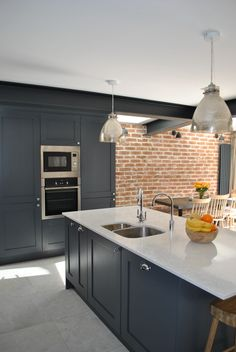 Modern shaker kitchen in dark slate blue looks stunning against the brick wall. The cabinets are complemented by marble effect quartz worktop. Bronze mirror splashback adds the wow factor to this modern extension . The island faces the back garden and this lay-out provides not just additional storage and seating but also leaves plenty of room for a dining table and sofa for a young growing family.
