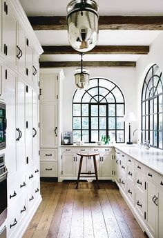 The arched windows, white on white palette, cross-beams, and reflective pendants make this narrow kitchen look bright and spacious.  Great use of textiles.