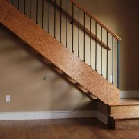 Clean simple stair with wood hand rail and metal balusters.