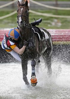 Elaine Pen of the Netherlands falls from her horse Vira as she competes in the equestrian eventing cross-country phase at the 2012 Summer Olympics, Monday, July 30, 2012, in London. (AP Photo/Markus Schreiber)