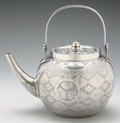 ¤ A silver tea kettle Taisho period (early century) Of disc form with cylindrical spout engraved with geometric patterns and with triple-aoi mon, the slightly concave cover surmounted by a pierced floral finial, the loop handle hinged 5 high Taisho Period, Silver Teapot, Teapots And Cups, Tea Art, Tea Service, Chocolate Pots, My Tea, Tea Accessories, Vintage Tea