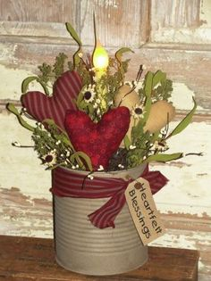 I have added a grungy ivory finish to this tin and then filled it with three of my primitive hearts, dried floral and berries. I have added a homespun tie around it with a grungy tag that says Heartfelt Blessings. In the back I have accented the arrangement with a electric light with a silicone bulb. HEART PRINTS MAY VARY SLIGHTLY DUE TO AVAILABILITY AT THE TIME OF YOUR ORDER, BUT WILL BE SIMILIAR TO THE ONES SHOWN IN THIS ARRANGEMENT. Meas