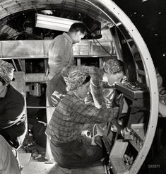 """December 1942. """"Production of B-17 heavy bomber. A skilled team of men and women workers at the Boeing plant in Seattle complete assembly and fitting operations on the interior of a fuselage section for a new B-17F (Flying Fortress) bomber. About half of the workers at the Boeing plant are women."""" Photo by Andreas Feininger for the Office of War Information."""