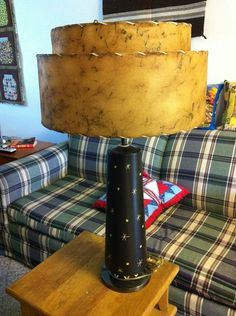 """This is my own fabulous MCM lamp. The body is brown ceramic with cream starbursts and hairpin legs sitting on a brass weighted base. The shade is a double-tiered fiberglass made to look like rawhide with leather lacing. Overall I think it's about 30"""" tall? There are no marks or labels on it, so I know nothing about it. It """"works"""", but probably should be rewired--the switch is temperamental."""