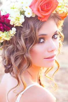 Instead of the flowers wearing a flower hat they would be wearing real flowers made into headpieces. There hair will be curly put into a messy bun just like this one and there makeup will match there natural skin color with light pink lips.