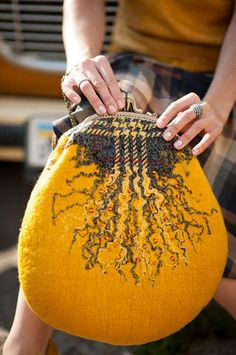 fibres unraveled from a piece of wool needle felted to make a larger wool purse from a small one