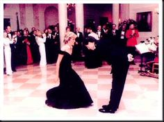 John Travolta bowing to Diana before dancing with her. She returns the gesture.