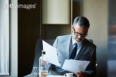 Businessman reading documents in hotel room - gettyimageskorea