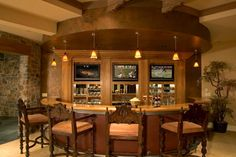 Fantastic home bar design with a curved bar and comfortable wood bar stools. From 1 of 30 projects by Gelotte Hommas.