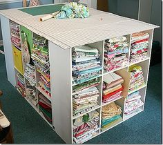 Is your fabric neatly organized and easy to find?  If not, this ingenious idea might be an option for you!  By taking four cube style shelves and topping them with a cutting board you can get all of your fabric organized AND have the perfect cutting table!