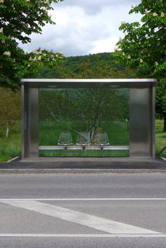 Ticket To Ride: Vitra Bus Stop By Jasper Morrison- Jasper Morrison designed the bus stops at the Vitra Campus in Germany in 2006. The bus stops, typical of his pared back style, are made made from polished steel and glass and feature Eames wire chairs mounted to them. © Alex James Bruce 2013