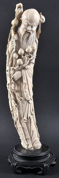 A GOOD EARLY 20TH CENTURY CHINESE CARVED IVORY FIGURE OF SAGE modelled holding a dragon staff and flowering peach vines. Ivory 1ft 4.5ins high.