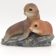 SOLD - Vintage pre-owned decorative collectible HOMCO seal figurine.  The bisque porcelain ceramic figurine features two baby lounging on a rock base.